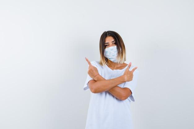 젊은 여성 t- 셔츠, 마스크를 가리키는 자신감, 전면보기를 찾고.