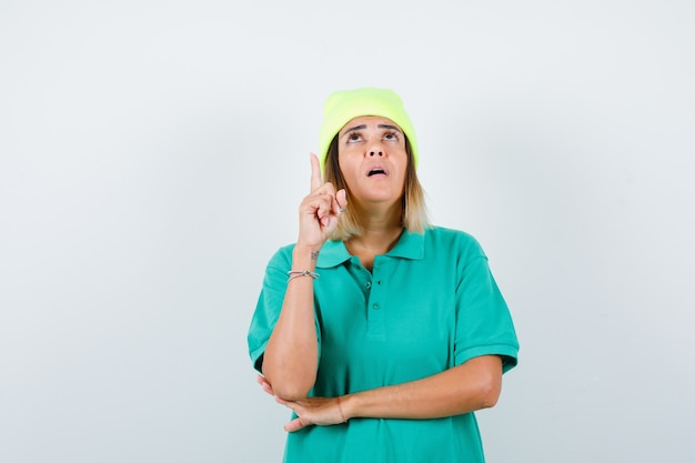 Giovane femmina rivolta verso l'alto, guardando verso l'alto in t-shirt polo, berretto e guardando pensieroso. vista frontale.