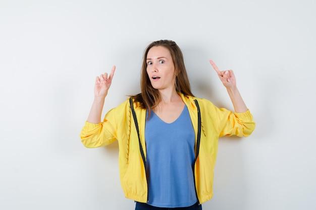 Giovane femmina che indica in t-shirt, giacca e guardando curiosa, vista frontale.