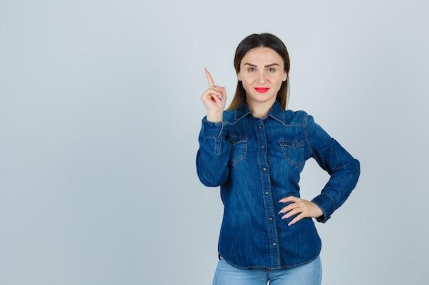 デニムシャツとジーンズで腰に手を保ち、陽気に見えながら上向きの若い女性