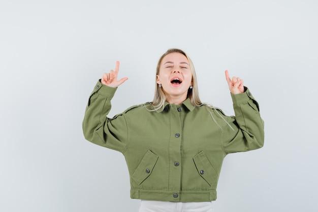 녹색 재킷, 청바지, 전면보기에서 비명 동안 가리키는 젊은 여성.