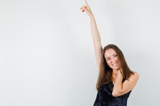 黒い一重項で首に手を上げて幸せそうに見える若い女性。