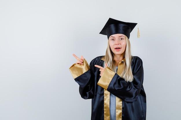 Giovane donna che punta all'angolo in alto a sinistra in uniforme da laureato e sembra stupita.
