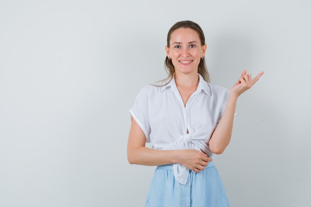 Giovane donna che punta all'angolo in alto a destra in camicetta, gonna e sguardo allegro