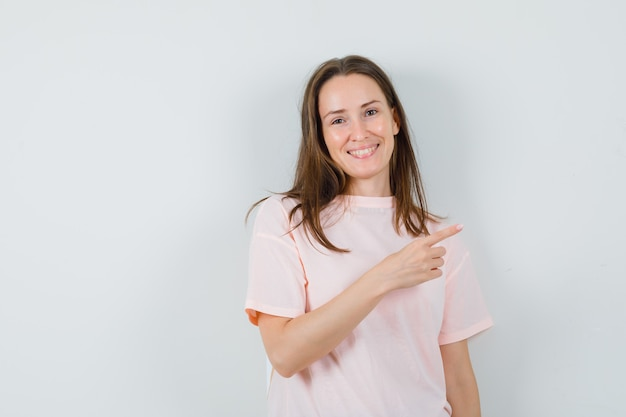 Young female pointing at upper right corner in pink t-shirt and looking happy. front view.
