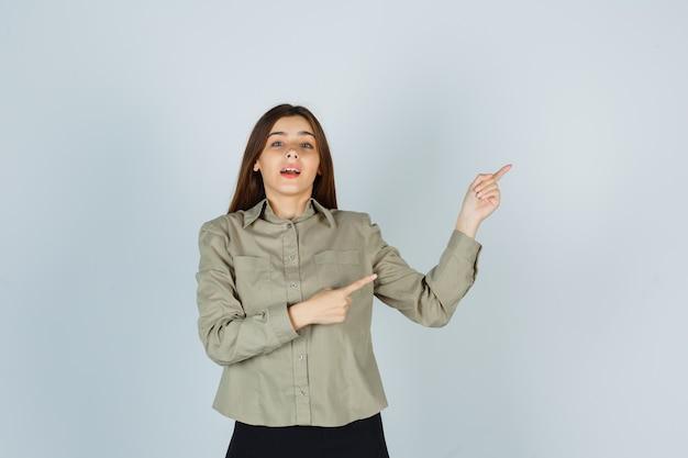 Giovane donna che punta all'angolo in alto a destra in camicia, gonna e sembra positiva. vista frontale.