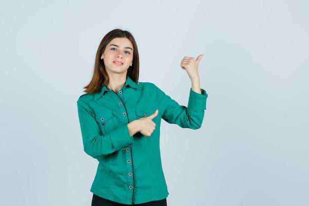 Giovane donna che punta all'angolo in alto a destra con i pollici in camicia verde e guardando allegro. vista frontale.