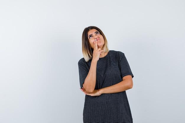 Giovane donna in abito polo in piedi nella posa di pensiero e guardando pensieroso, vista frontale.