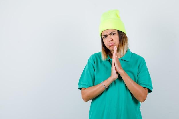 Giovane donna in t-shirt polo, berretto con le mani in gesto di preghiera e sguardo sconvolto, vista frontale.