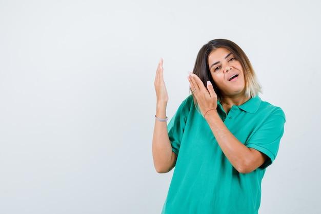 Giovane femmina in t-shirt polo che mostra qualcosa con le palme e guardando beata, vista frontale.