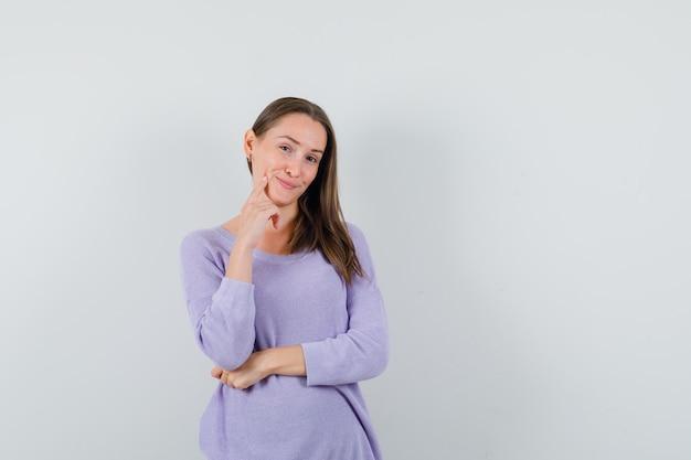 Giovane donna in posa in camicetta lilla e che sembra carina. vista frontale. spazio per il testo