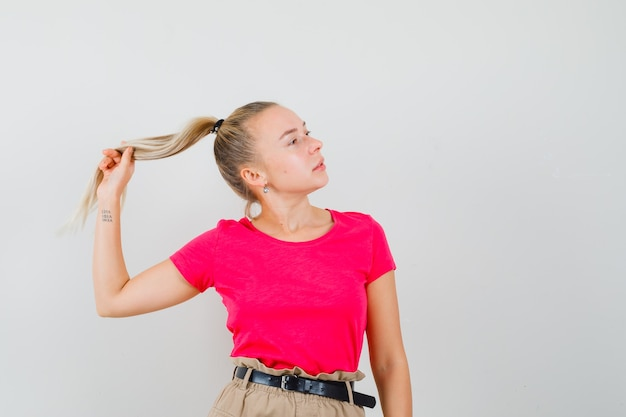 Tシャツ、パンツ、キュートに見える彼女のストランドを保持しながらポーズをとる若い女性。正面図。