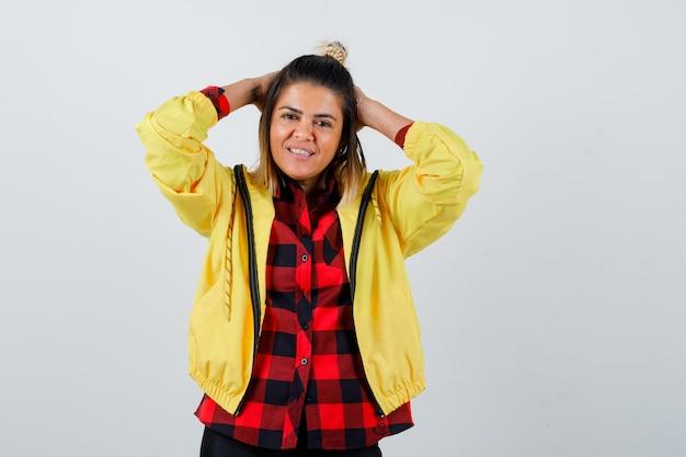 市松模様のシャツ、ジャケット、陽気に見える、正面図で頭の後ろに手を保ちながらポーズをとる若い女性。