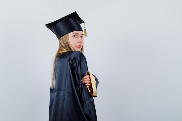대학원 유니폼을 입고 카메라를 보면서 매력적인 젊은 여성 포즈. .
