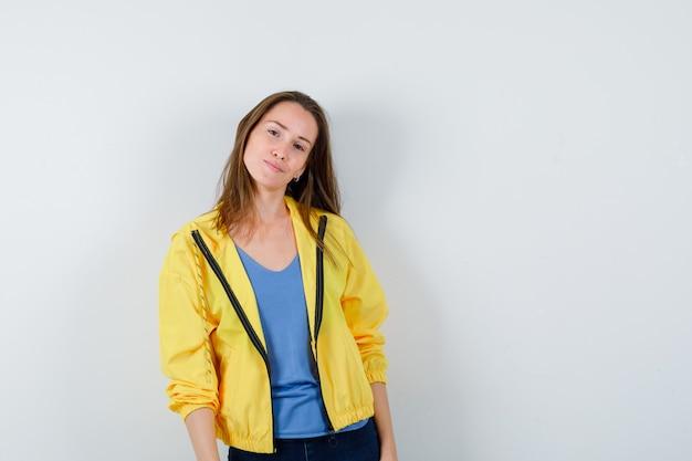 Tシャツ、ジャケット、華やかな正面図でカメラを見ながらポーズをとる若い女性。