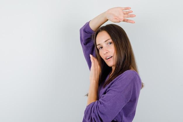 Молодая женщина позирует, глядя на камеру в фиолетовой рубашке и выглядит мило. .