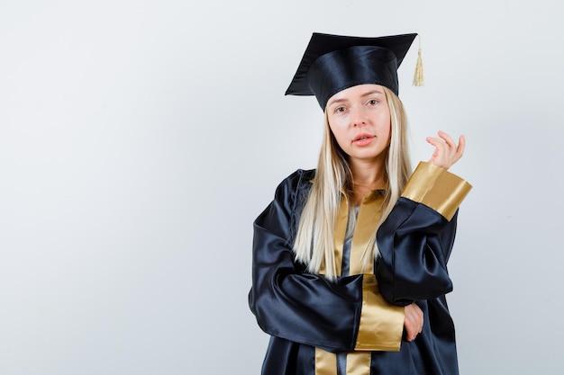 Giovane donna in posa mentre guarda la telecamera in uniforme da laureato e sembra carina.