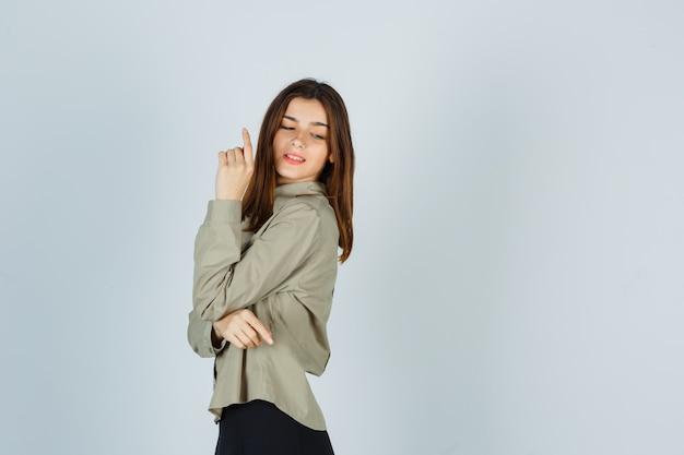 셔츠에 그녀의 어깨 너머로 보면서 포즈를 취하는 젊은 여성