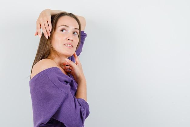 Giovane donna in posa mentre cerca in camicia viola e sembra allettante.