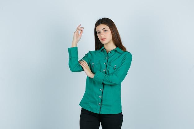 녹색 셔츠, 바지에 손을 올리고 화려한 찾고있는 동안 젊은 여성 포즈. 전면보기.