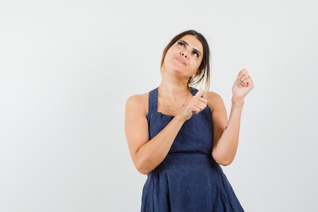 Giovane donna in posa mentre mostra pollice in su in abito blu scuro e sembra speranzosa