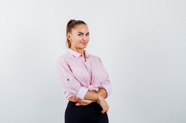 カジュアルなシャツに立って魅力的に見えながらポーズをとる若い女性。正面図。