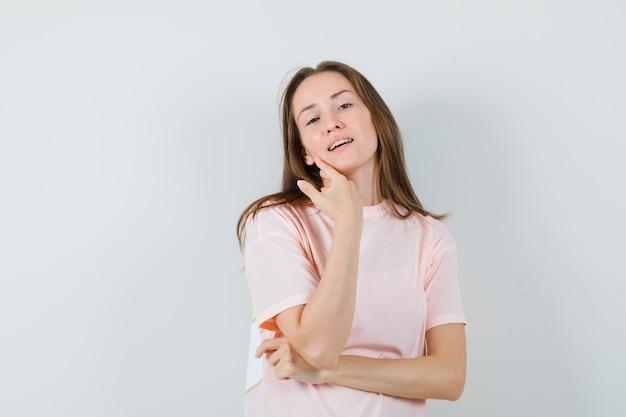 ピンクのtシャツに立って魅力的に見ながらポーズをとる若い女性。正面図。