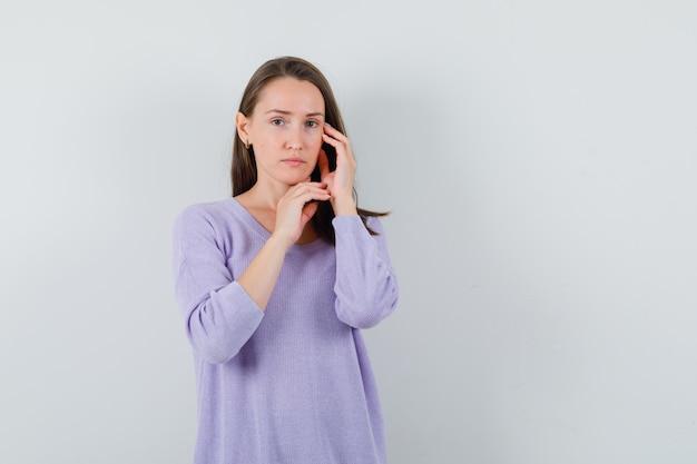 라일락 블라우스에 손으로 그녀의 얼굴을 만지고 현명한 찾고있는 동안 포즈를 취하는 젊은 여성. 전면보기.