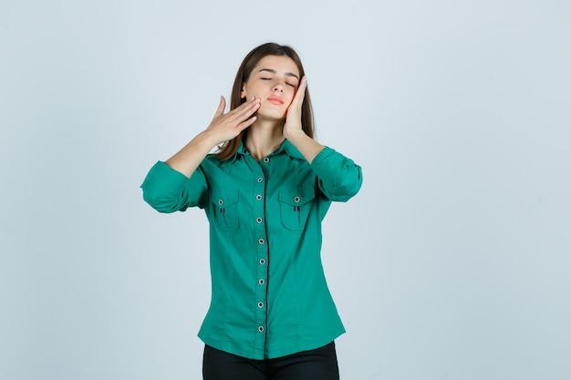 Молодая женщина позирует, касаясь кожи на щеках в зеленой рубашке и выглядя расслабленной, вид спереди.