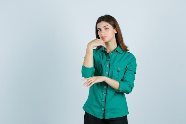 緑のシャツで彼女のあごの肌に触れながらポーズをとって、優雅な正面図を探している若い女性。