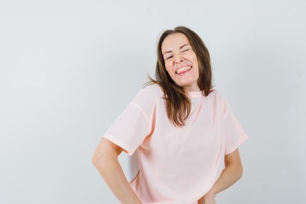 눈을 윙크하는 동안 포즈를 취하는 젊은 여성, 분홍색 티셔츠에 혀를 튀어 나와 행복을 찾고 있습니다. 전면보기.