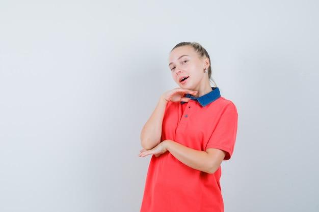 Молодая женщина позирует с подбородком, подперев рукой в футболке и выглядит красиво, вид спереди.