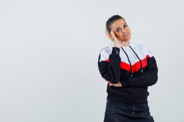 화려한 셔츠, 전면보기에에서 머리에 손으로 포즈 젊은 여성.