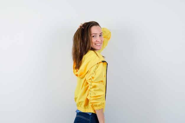 Молодая женщина позирует с рукой на голове в желтой куртке и выглядит заманчиво.