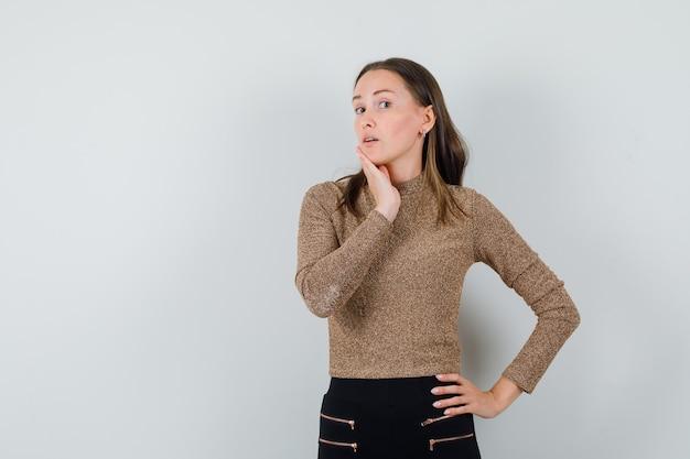 金色のブラウスを着て顎に手を当ててポーズをとって、印象的な若い女性。正面図。テキスト用のスペース