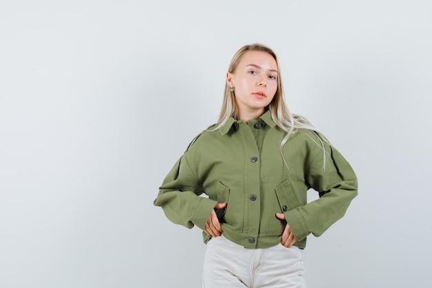 Молодая женщина позирует с руками в кармане в вид спереди зеленой куртке.