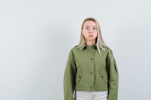 緑のジャケットで彼女の唇をふくれっ面と落ち着いて見える若い女性、正面図。