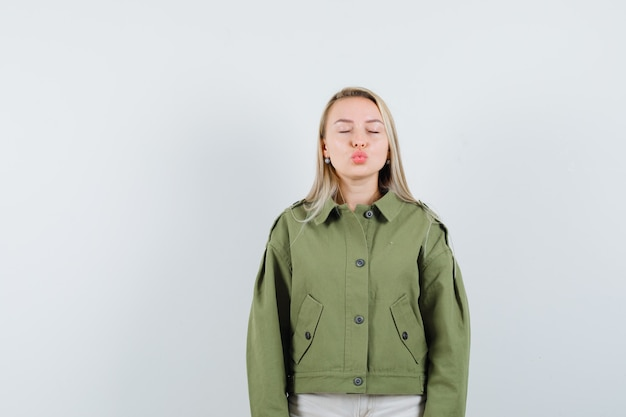 緑のジャケット、ジーンズ、正面図で目を閉じながら唇をふくれっ面の若い女性。
