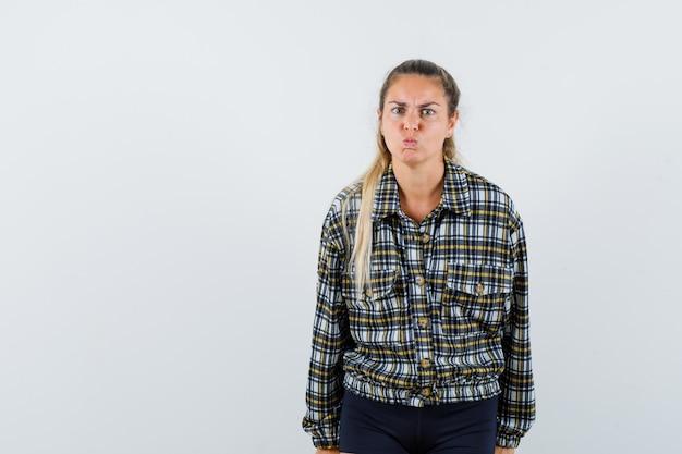 若い女性のふくれっ面の唇、シャツの眉をひそめている顔、ショートパンツと意地悪な顔、正面図。