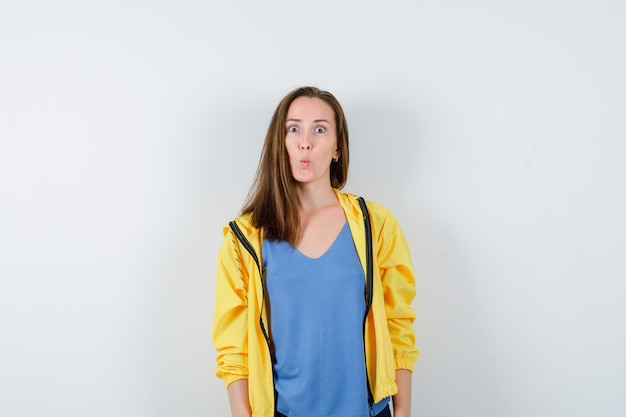 젊은 여성 t- 셔츠, 재킷에 입술을 삐 죽 하 고 놀란, 전면보기를 찾고.