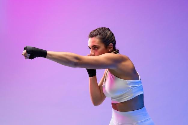 Молодая женщина занимается кикбоксингом