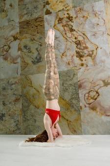Молодая женщина упражнениями йоги на голове в помещении