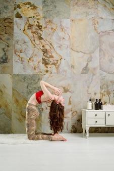 Молодая женщина практикует йогу устрасана верблюжья вариация позы в помещении