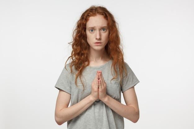 기도하고 비참함을 느끼는 젊은 여성