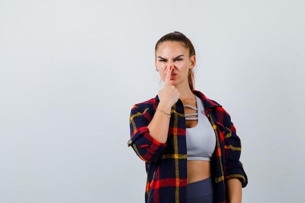 Giovane donna che preme il dito sul naso in top corto, camicia a scacchi, pantaloni e aspetto divertente. vista frontale.