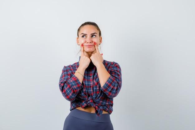 市松模様のシャツ、ズボン、思慮深く見える、正面図で頬に指を押す若い女性。