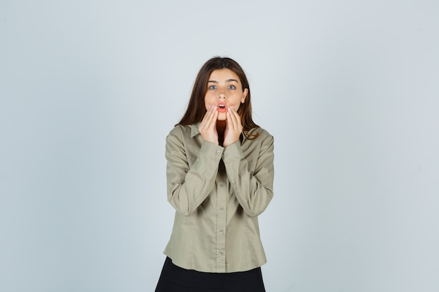 Молодая женщина сжимает руки в рубашке, юбке и выглядит шокированной