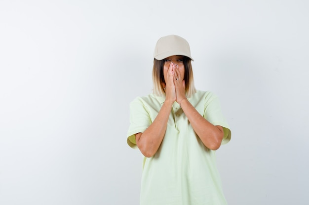 Young female pressing hands together on face in t-shirt, cap and looking wistful. front view.