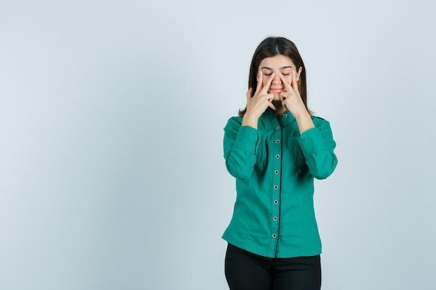 Giovane donna che finge di strofinare la maschera per il viso intorno alla zona del naso in camicia verde, pantaloni e sguardo calmo, vista frontale.