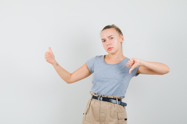 Tシャツ、ズボンを親指で下に向けて何かを見せているふりをして、がっかりしている若い女性。正面図。